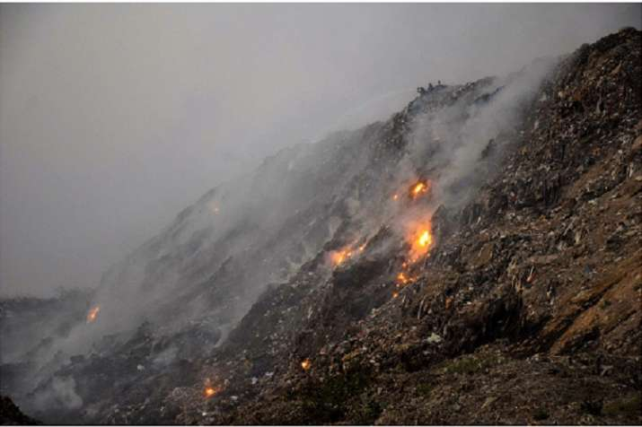 India Tv - Smoke rises after a fire broke out at Bhalswa landfill site in New Delhi, Monday, Oct 22, 2018. A fire has been raging at the landfill site since October 20, raising concerns about rising pollution levels in the city as air quality oscillated between