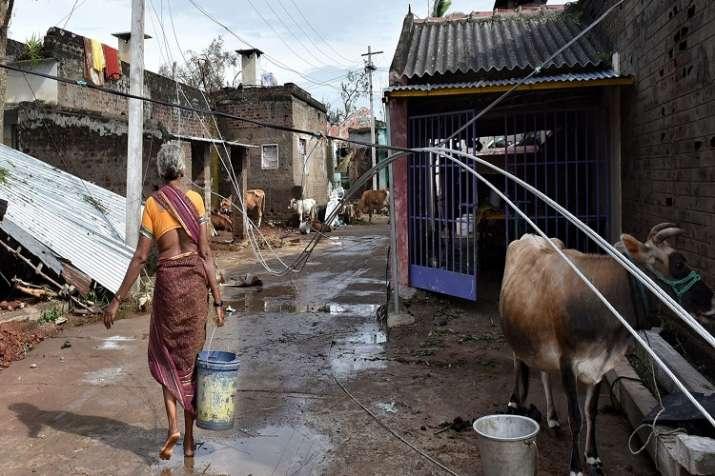 India Tv - A woman walks through an area hit by cyclone 'Titli', in Srikakulam.