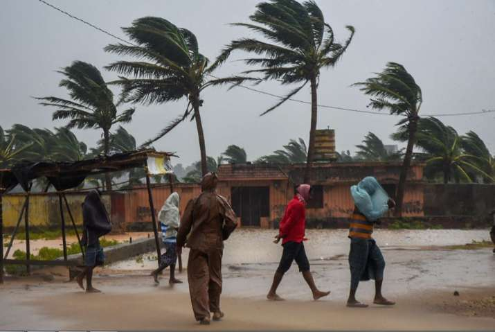 India Tv - People make their way as Cyclone Titli hits the city, starting with surface wind effect reaching speeds of 126 kmph at Gopalpur, in Ganjam,