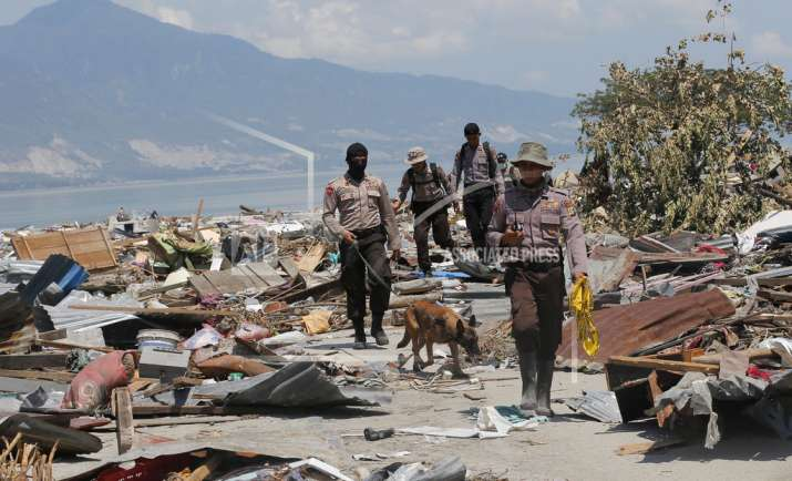India Tv - A police K9 unit continues to search for victims in the wreckage following earthquakes and a tsunami in Indonesia.