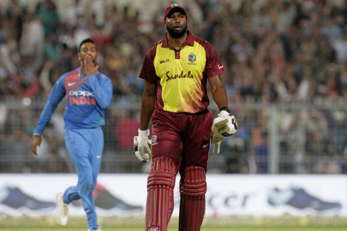 India Tv - Krunal Pandya, left, celebrates as West Indies' Kieron Pollard, right, leaves the field after being dismissed.