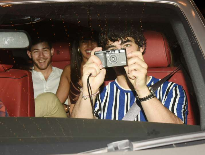 India Tv - While in the car when the paps tried to click pictures of the two couples, Joe Jonas was spotted clicking the paparazzi instead.