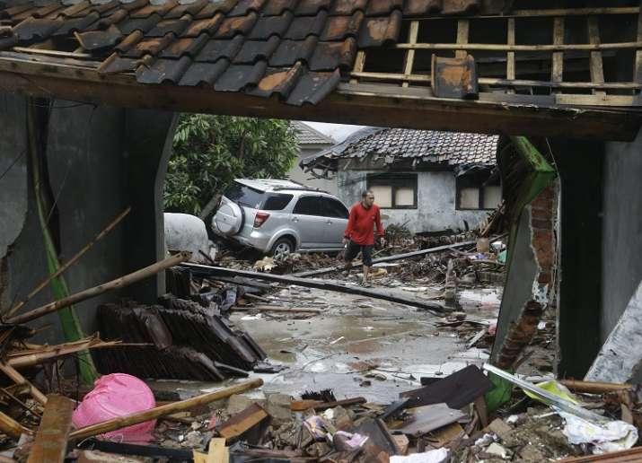 A man walks near debris at a tsunami-ravaged area in