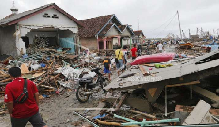 India Tv - People inspect the damage at a tsunami-ravaged village in Sumur, Indonesia. (AP Photo/Tatan Syuflana)