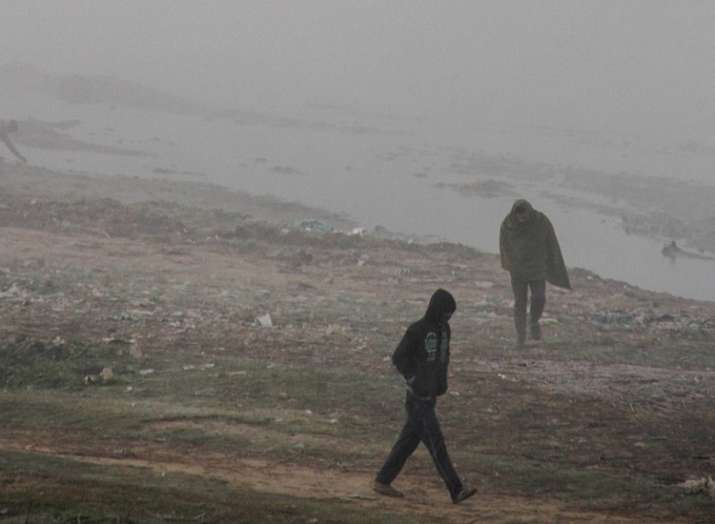 India Tv - People walk across a thick fog on a cold, winter morning, in Jammu