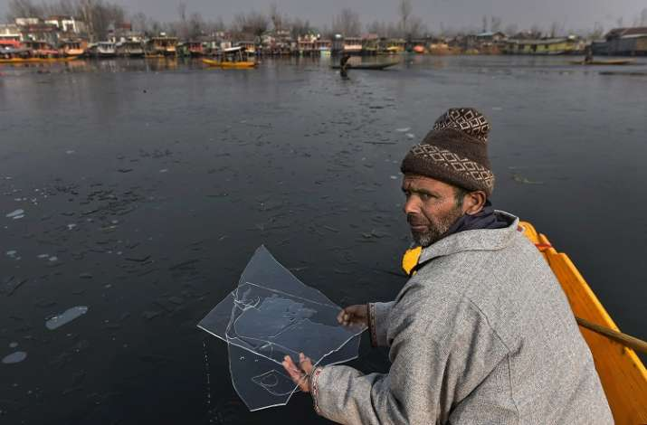 A boatman holds ice flakes from the partially frozen Dal