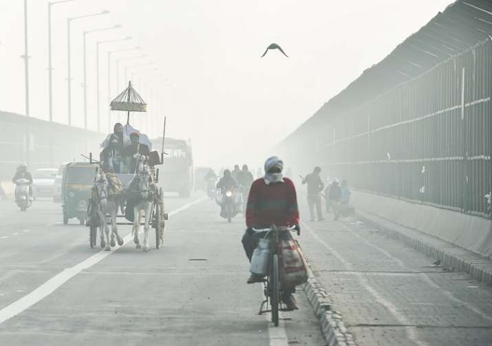 Commuters ride through heavy fog on a winter morning, in