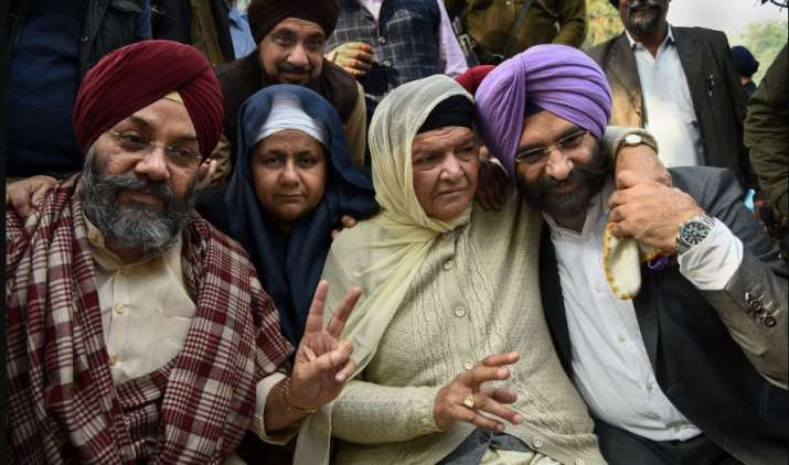 India Tv - New Delhi: (L-R) DSGMC President Manjit Singh GK, Nirpreet Kaur and Jagdish Kaur, whose family members were killed during 1984 anti-Sikh riots, Akali Dal MLA Manjinder Singh Sirsa and others react after the Delhi High Court convicted Congress leader Sajjan Kumar for criminal conspiracy, promoting enmity, acts against communal harmony in the 1984 anti-Sikh riots and sentenced him to life imprisonment, in New Delhi, Monday, Dec. 17, 2018.