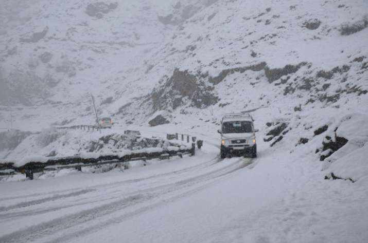 India Tv - Lahaul-Spiti: Vehicles slowly make their way over the snow-covered road during snowfall at Kyelang