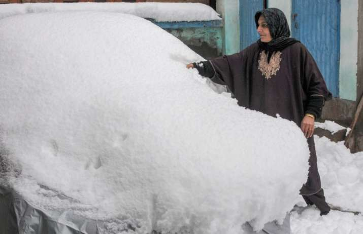 India Tv -  A woman clears the snow off a car, in Downtown Srinagar