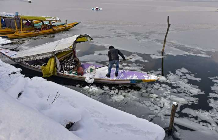 India Tv - A man clears snow of his boat after heavy snowfall, in Srinagar