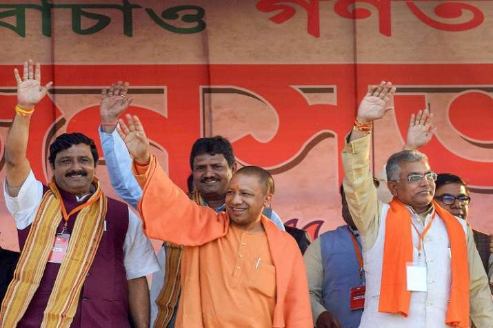 India Tv - Uttar Pradesh Chief Minister Yogi Adityanath along with State BJP president Dilip Ghosh and party leader Rahul Sinha waves at the crowd during a rally in Purulia district of West Bengal.