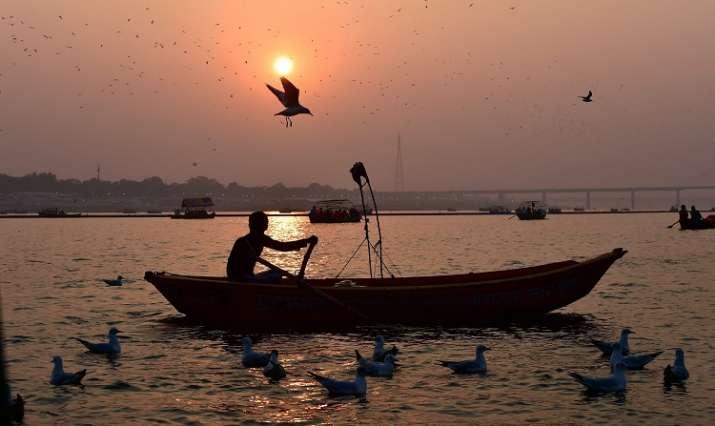 India Tv - A man sails his boat as sunset during the Kumbh Mela 2019 at the Sangam in Allahabad