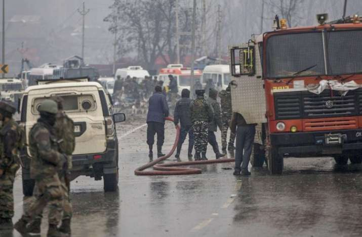 India Tv -   Firemen spray water on a road to wash away the blood stains at the site of suicide bomb attack at Lathepora Awantipora in Pulwama district of south Kashmir. (PTI Photo)