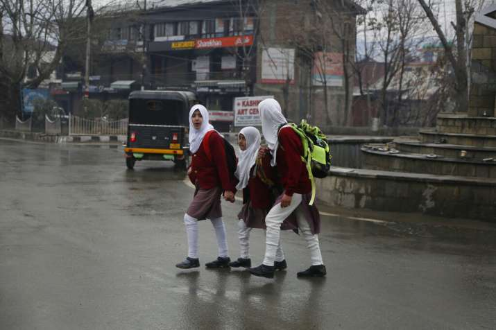 India Tv - Kashmiri school girls walk to their school early morning in Srinagar, Monday, March 11, 2019. Schools in Indian Kashmir reopened Monday after a three months winter break. (AP Photo)