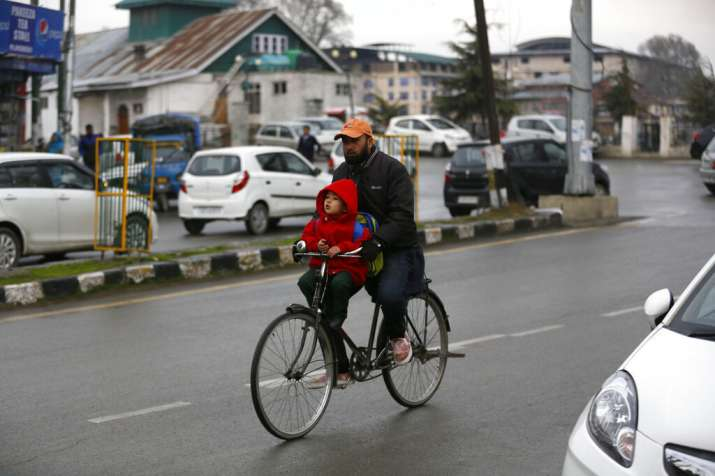 India Tv - A Kashmiri man carries a boy to school on a bicycle in Srinagar, Monday, March 11, 2019. Schools in Indian Kashmir reopened Monday after a three months winter break. (AP Photo)