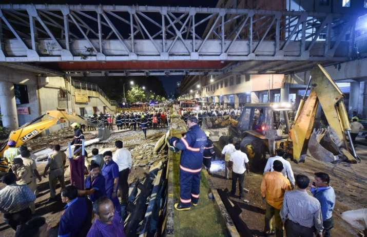India Tv - Mumbai: Rescue worker clear away debris of a collapsed foot overbridge