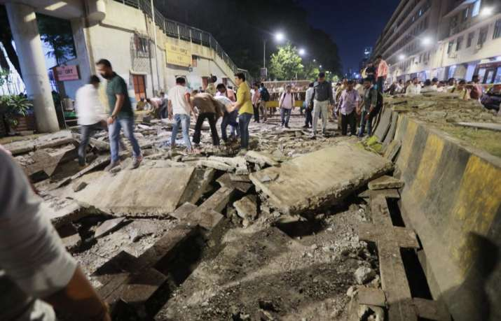 India Tv - Mumbai: A general view shows a part of the partially collapsed foot overbridge near a train station