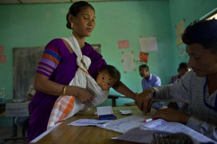 India Tv - A polling official collects the thumb impression from a Mishing tribal woman carrying an infant during the first phase of general elections in Majuli, Assam.