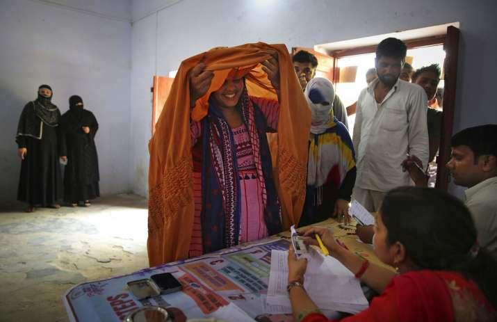 India Tv - A Muslim woman lifts her veil to identity herself to a polling agent before casting her vote in village Shahpur near Muzaffarnagar, Uttar Pradesh.