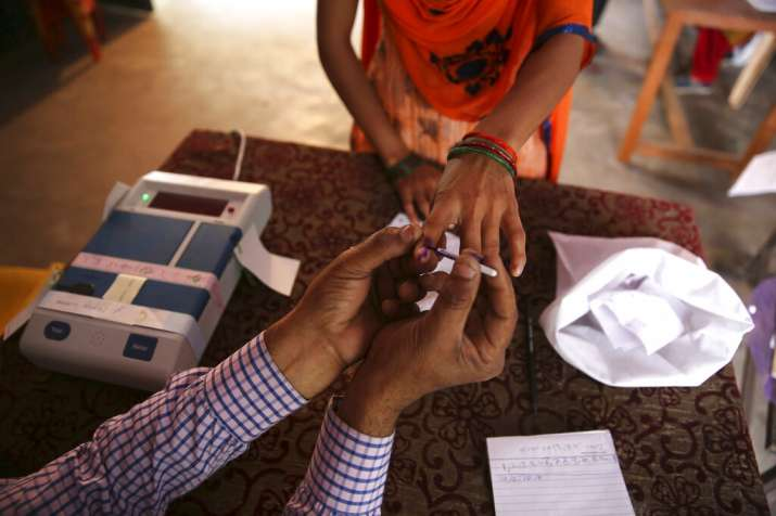 India Tv - A polling officer puts indelible ink mark on the index finger of a voter for the first phase of general elections, near Ghaziabad.