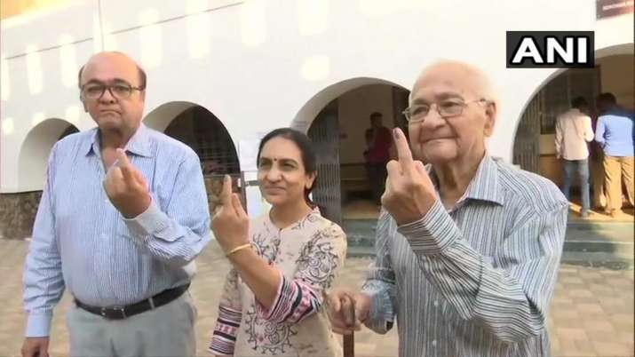 India Tv - Maharashtra: A 92 year old voter DN Sanghani accompanied by his son and daughter in law after casting their votes at a polling booth in Gondia.