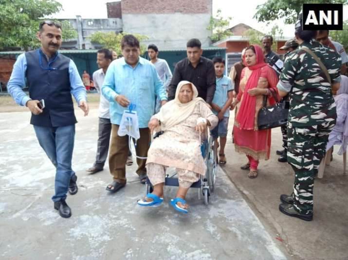 India Tv - Jammu & Kashmir: An 80-year-old patient, Jogindero Devi, comes from Kathua district hospital at polling booth, in Kathua, to cast her vote