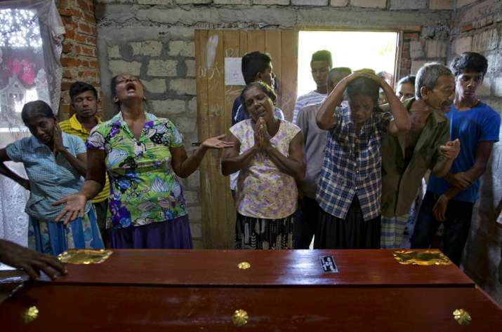 Relatives weep near the coffin with the remains of 12-year