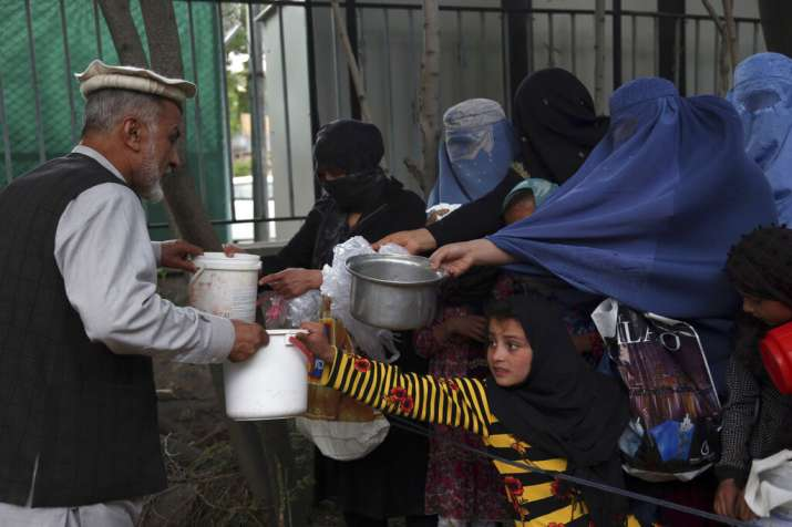 India Tv - Afghanistan Ramadan:Afghan families receive free food donated by other villagers as they prepare to break their fast during the holy month of Ramadan, in Kabul, Afghanistan, Sunday, May 12, 2019. (AP Photo/Rahmat Gul)