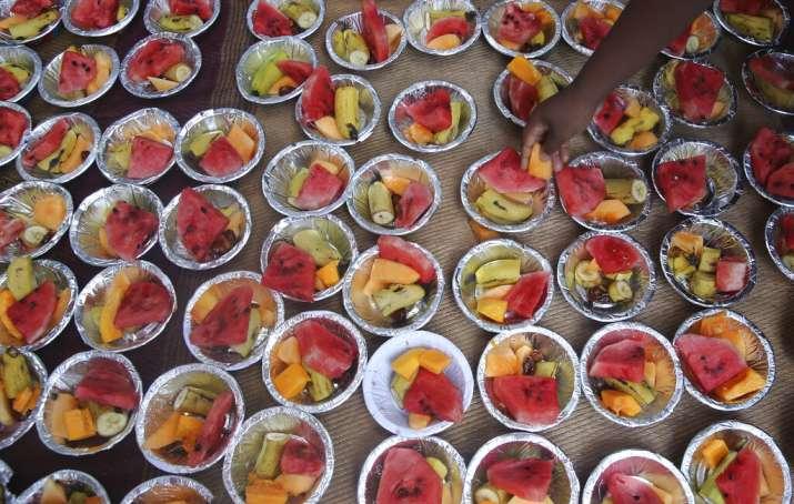 India Tv - A volunteer puts fruits in a bowl to distribute at the shrine of Makhdoom Ali Shah Mahimi in Mumbai, India, Sunday, May 12, 2019.
