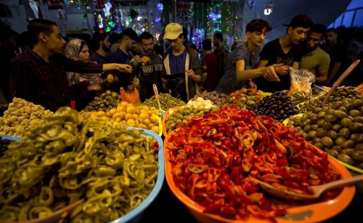 India Tv - Palestinian Ramadan: Palestinians look at pickles on sale for Ramadan for the month of Ramadan, at the main market in Gaza City, Tuesday, May. 7, 2019.