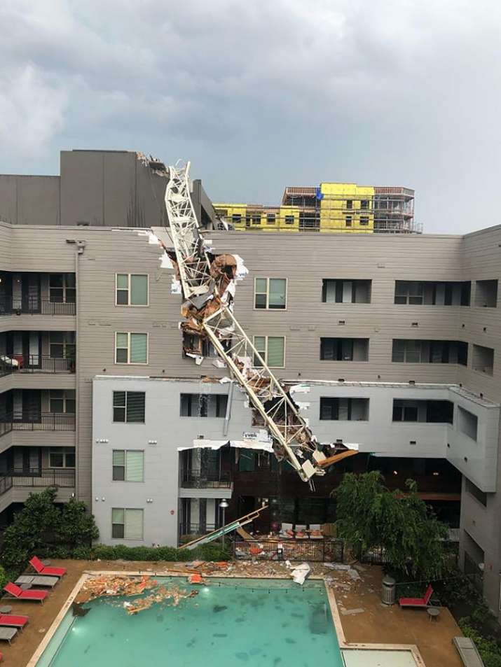 India Tv - Construction crane falls on building during storm