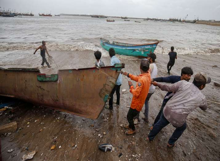 Fishermen move their boats to a safer place along the shore