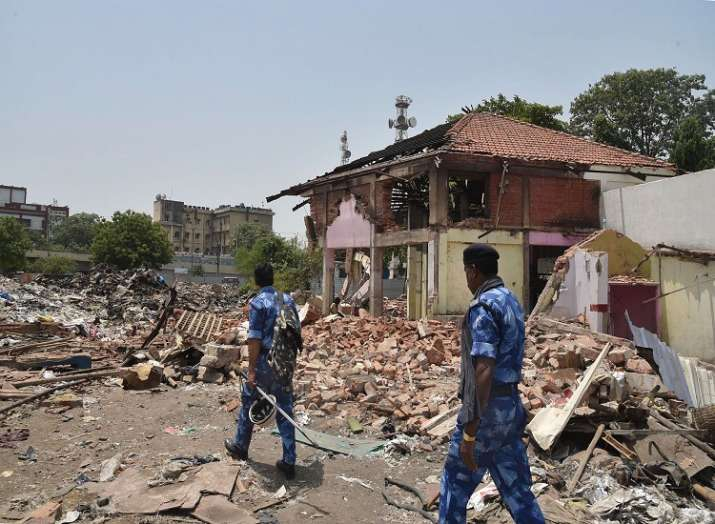 Security personnel make way through the debris of
