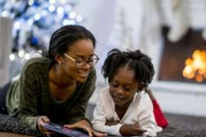 Parent and kid reading book together