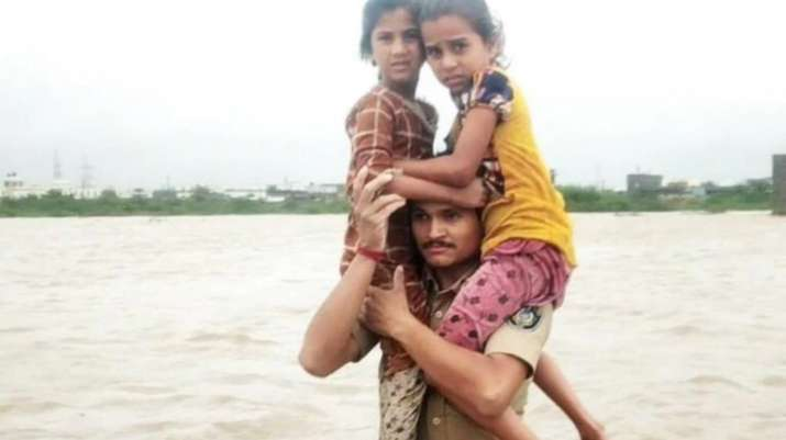 Heroic rescue: Gujarat cop carries two girls on his