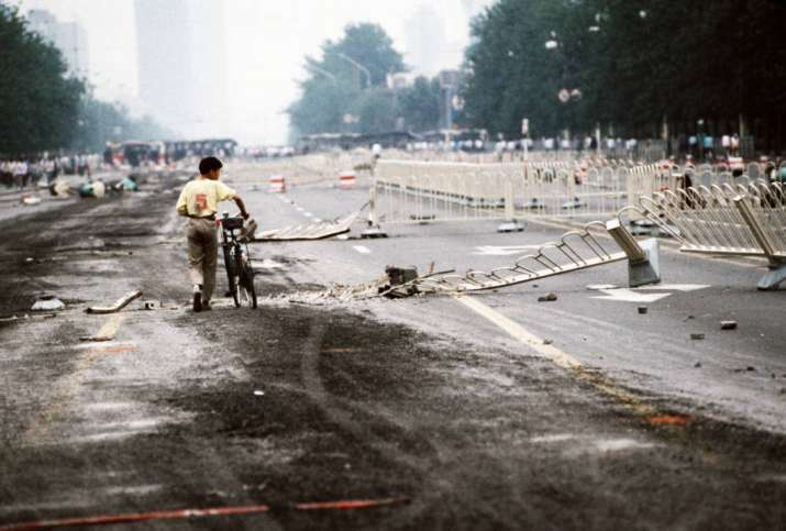 India Tv - A lone cyclist walks past street barriers on Changan Avenue, crushed by Chinese Army tanks during the Tiananmen Square massacre on June 4.