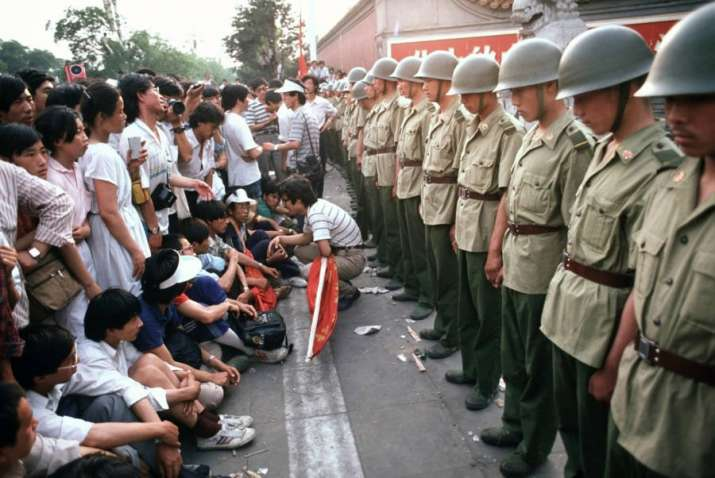 India Tv - Demonstrators sit in front of soldiers standing guard outside the Chinese Communist Party's headquarters on Changan Avenue a few days before the start of the violence. June 1.