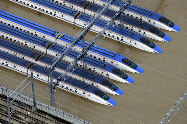 India Tv - Bullet trains are seen submerged in muddy waters in Nagano, central Japan.
