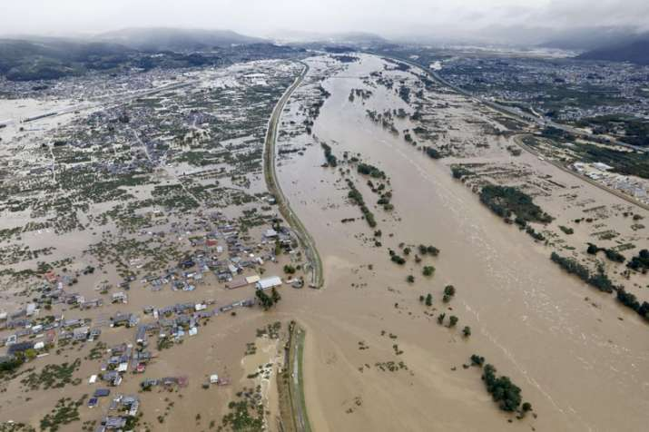 India Tv - Residential area, left, are submerged in muddy waters after an embankment of the Chikuma River broke because of Typhoon Hagibis.