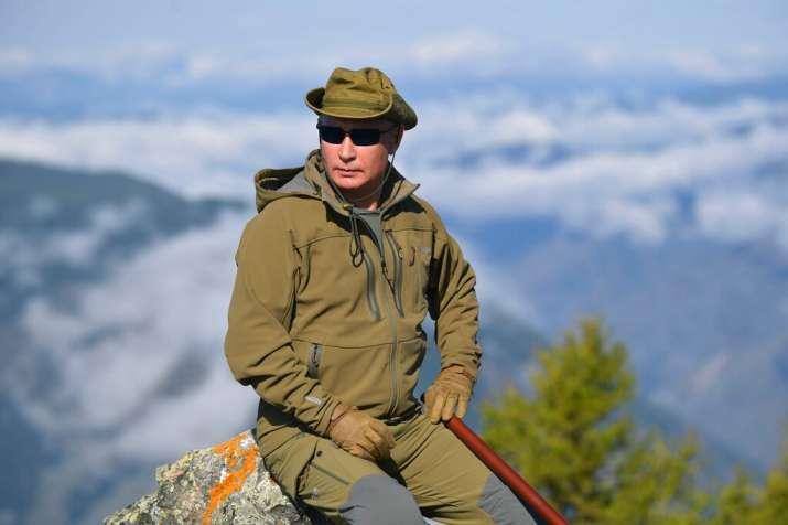 Russian President Vladimir Putin rests on a hill in Siberia