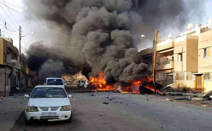 India Tv - This photo by Hawar news, the news agency for the semi-autonomous Kurdish areas in Syria (ANHA), shows flames rising from burned cars at the site of an explosion in the central Qamishli city in northeastern Syria, Friday, Oct. 11, 2019. Activists and Syrian Kurdish officials are reporting a large explosion outside a popular fast food restaurant. It was not clear what caused the explosion on Friday which occurred amid intensive shelling by the Turkish military in the city and other areas.