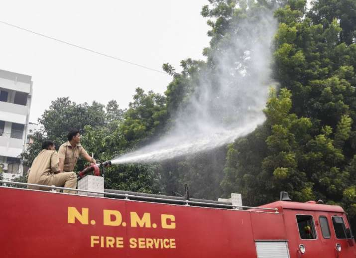India Tv - A water tanker sprays water into the atmosphere to curb rising pollution at Patel Chowk