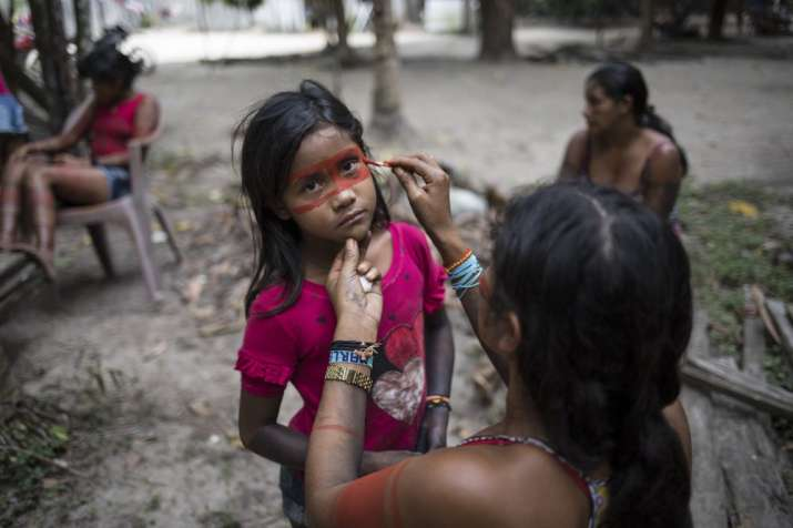 India Tv - They paint their faces with dyes from seeds to prepare for battle