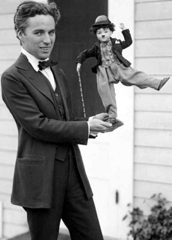India Tv - Charlie Chaplin without his mustache and makeup holding a doll of his own.