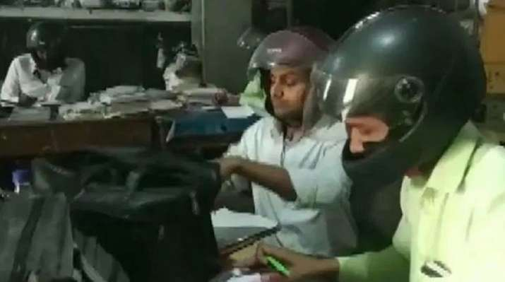 Employees wear helmets to work at government office in UP