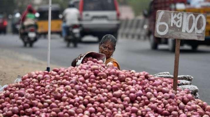 A woman arranging onions near a road in Chennai