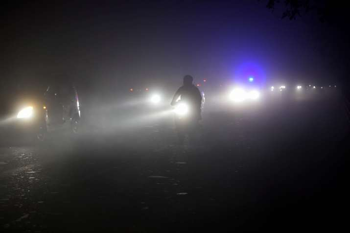 Vehicles ply at a road with headlights on during a cold and