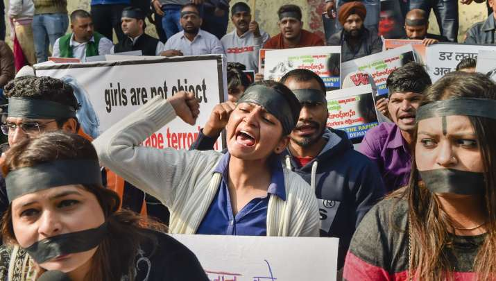 Protesters wearing black bands raise slogans during a