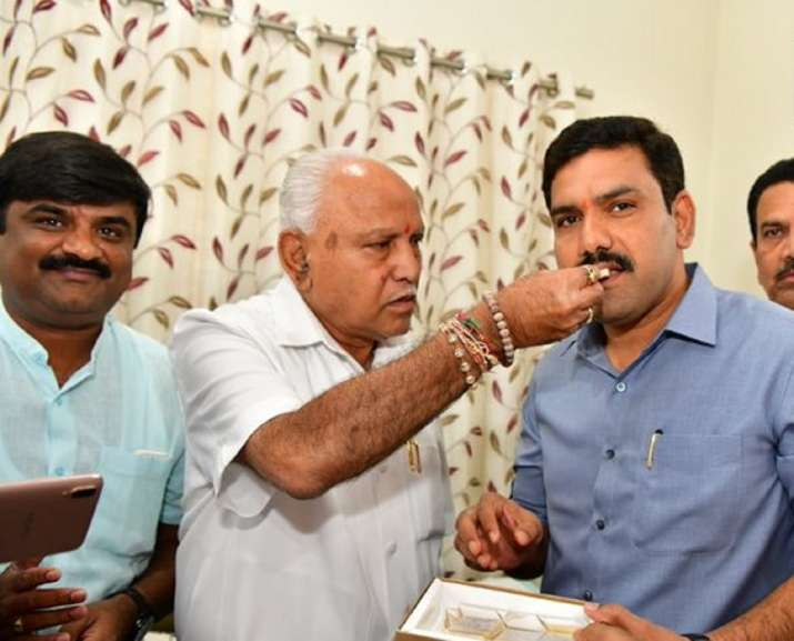 Yediyurappa celebrates with son as BJP set for majority in